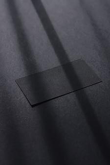 Biglietto da visita nero su sfondo flatlay scuro e ombre della luce del sole, design piatto del marchio di lusso e identità del marchio per i modelli
