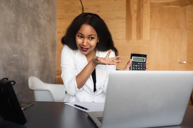 Donna nera di affari che per mezzo del computer portatile per analizzare i dati mercato azionario forex trading grafico borsa trading online concetto di investimento finanziario da vicino