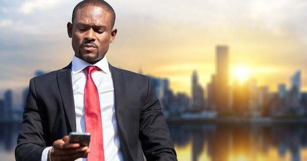Uomo d'affari nero usando il suo smartphone all'aperto contro uno skyline della città moderna