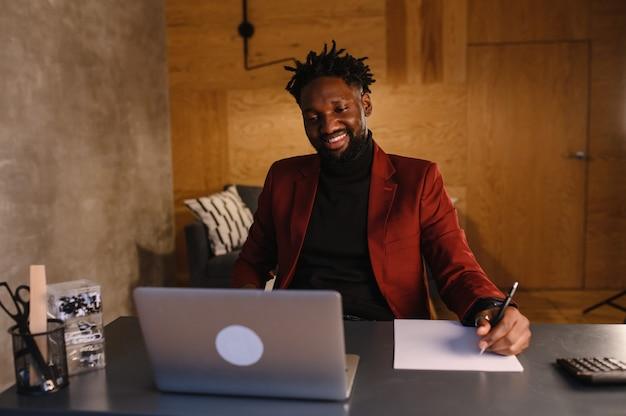 Uomo d'affari nero utilizzando laptop per analizzare i dati del mercato azionario