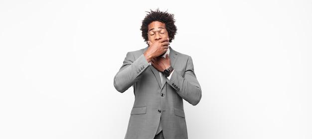 Uomo d'affari nero sensazione di malessere con mal di gola e sintomi influenzali, tosse con la bocca coperta