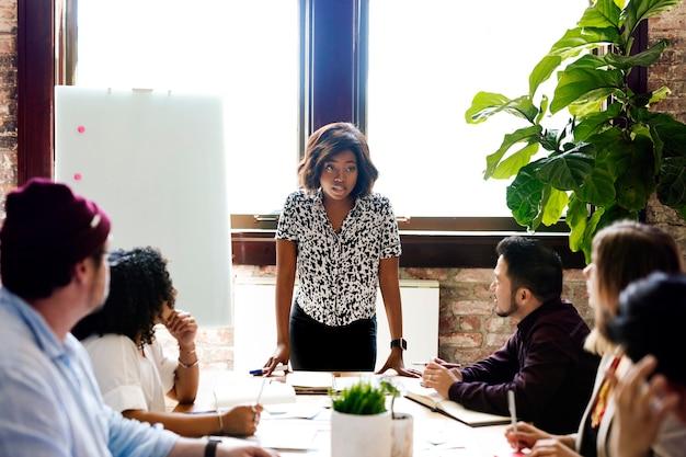 Donna d'affari nera che prende il comando nella sala riunioni meeting