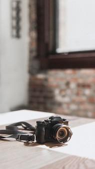 Fotocamera nera su uno sfondo del telefono cellulare da tavolo in legno