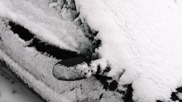 Macchina nera nella neve nel parcheggio.