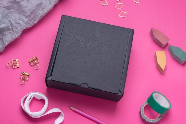 Scatola di cartone nera sulla scrivania in ufficio di colore