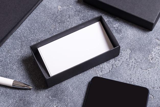 Scatola di cartone nera e biglietti da visita bianchi sulla scrivania in ufficio