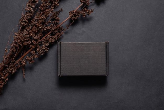 Scatola di cartone nera decorata con rami secchi mock up