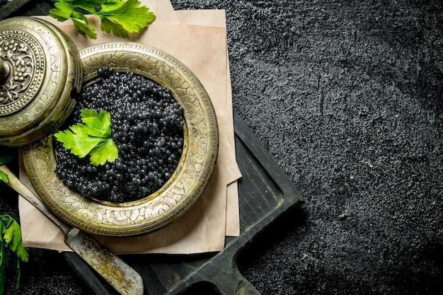 Caviale nero in una ciotola su un tagliere con prezzemolo. sul nero rustico