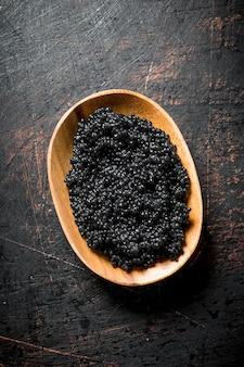 Caviale nero nella ciotola. sul tavolo rustico scuro
