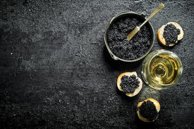 Caviale nero in una ciotola con panini e vino. sul nero rustico