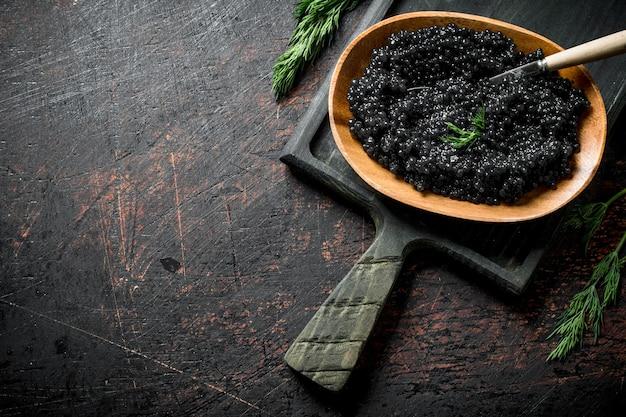 Caviale nero in una ciotola con un cucchiaio sul tagliere. su rustico scuro