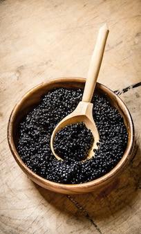Caviale nero in una ciotola con un cucchiaio di legno. su un tavolo di legno.