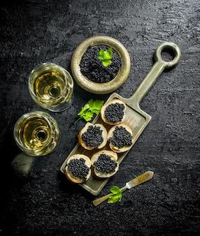 Caviale nero su fette di pane e vino. sul nero rustico