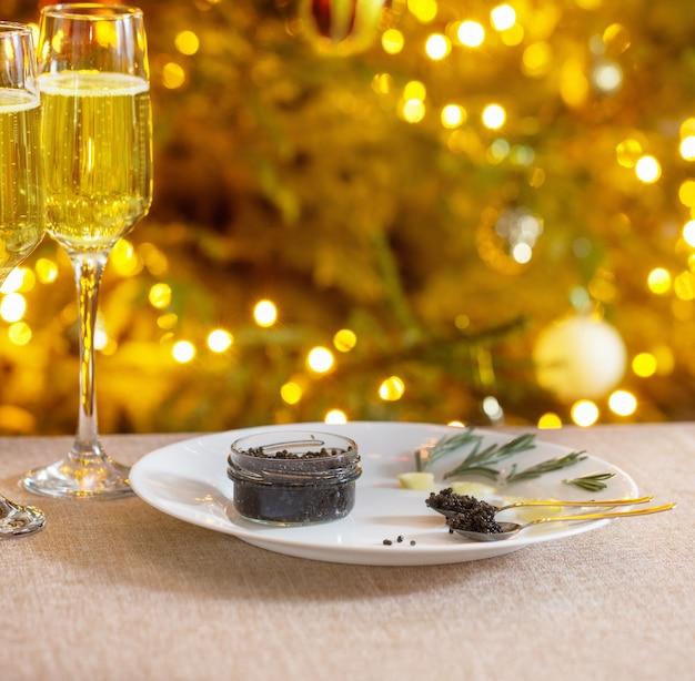 Caviale nero e bicchiere di champagne sull'albero di natale di sfondo