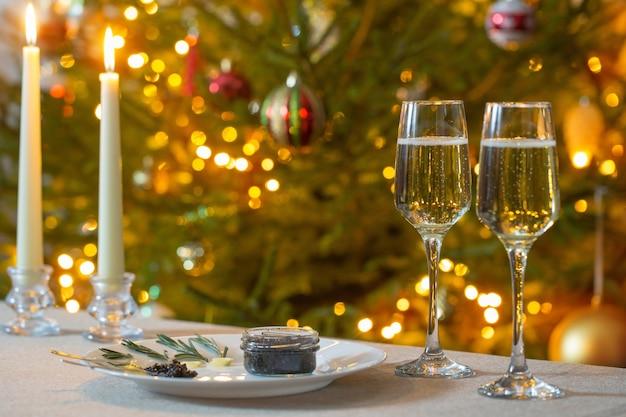 Caviale nero e bicchiere di champagne sull'albero di natale