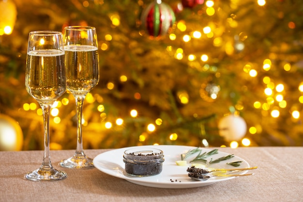 Caviale nero e bicchiere di champagne sull'albero di natale della parete