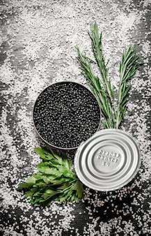 Caviale nero in un barattolo con erbe aromatiche e sale sul sale da tavola nero