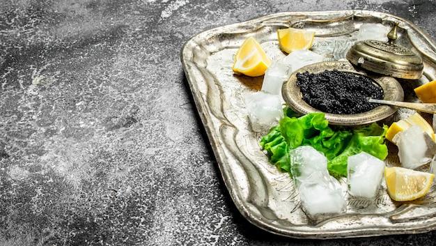 Caviale nero sulla vecchia vaschetta del ghiaccio. su fondo rustico.