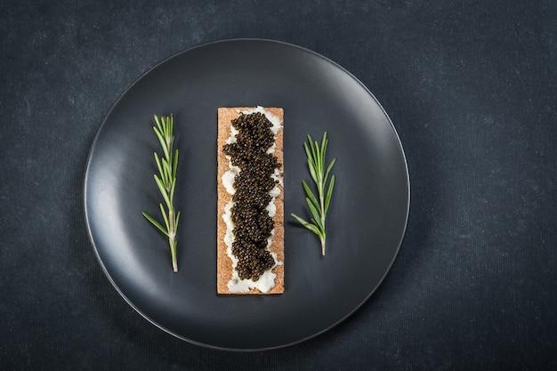 Caviale nero di storione nei biscotti con crema di formaggio. cucchiaio con caviale. piatto rotondo blu. superficie scura