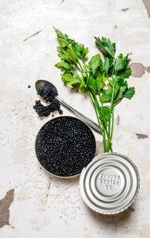 Caviale nero in un barattolo di latta con erbe su fondo rustico
