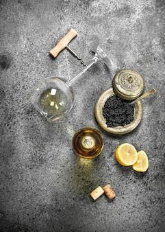 Caviale nero con un bicchiere di vino bianco. su fondo rustico.