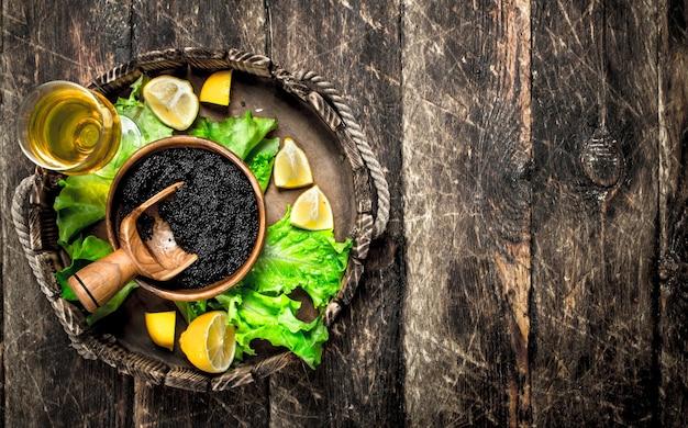 Caviale nero con un bicchiere di vino e verdure sulla tavola di legno.