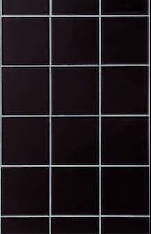 Reticolo delle mattonelle della parete del bagno in ceramica nera per lo sfondo. struttura della parete