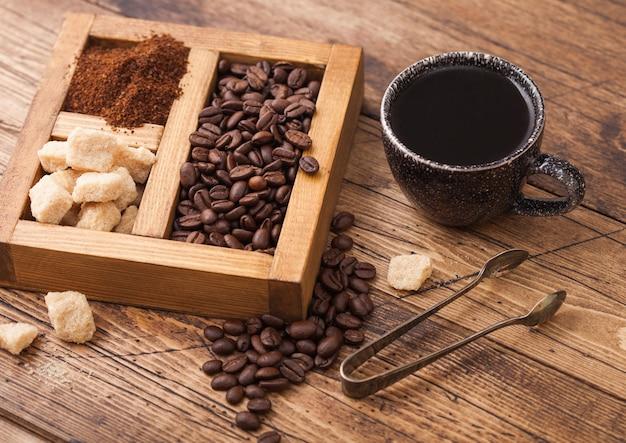Tazza in ceramica nera di caffè biologico crudo fresco con fagioli e polvere macinata con zucchero di canna in scatola vintage su fondo di legno.