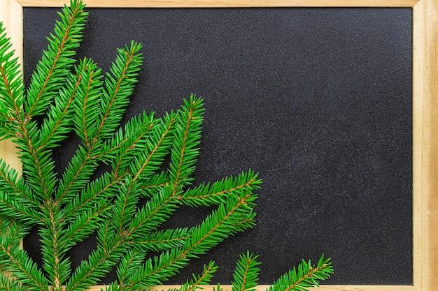Lavagna nera in una cornice di legno e un ramo di un albero nell'angolo.
