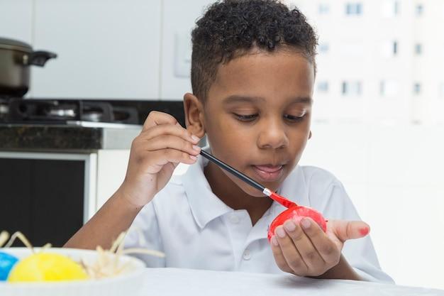 Bambino nero, uovo di pasqua rosso dipinto concentrato.