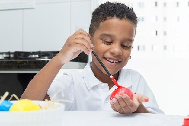 Bambino nero divertendosi a dipingere l'uovo di pasqua.