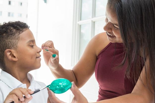 Bambino nero con gli occhi chiusi, in attesa che la madre si dipinga il naso per pasqua.