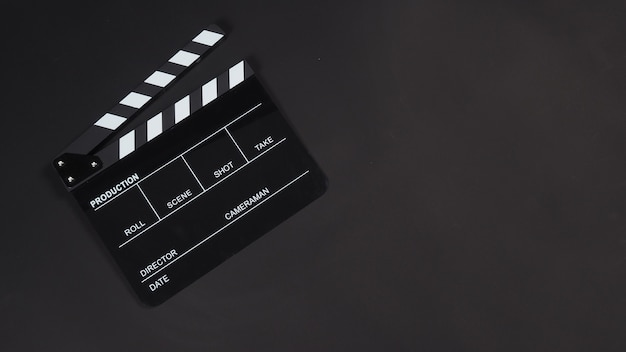 Black clapperboard o clap board o film ardesia utilizzare nella produzione di video, film, industria cinematografica su sfondo nero.