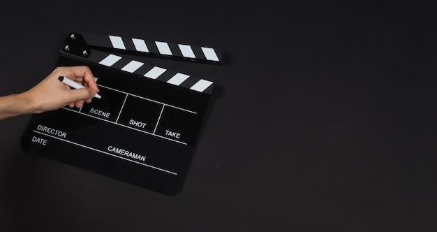 Black clapperboard o clap board o ardesia di film con uso di penna di tenuta a mano nella produzione di video, film, industria cinematografica su sfondo nero.