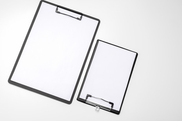 Appunti neri con foglio bianco bianco attaccato su bianco
