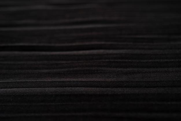 Primo piano dello sfondo della trama del panno nero plisse plissettato sfondo della gonna nera morbida trama satinata