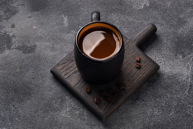Caffè nero in una tazza e chicchi di caffè su uno sfondo scuro. vista dall'alto copia spazio.
