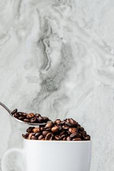 Caffè nero in tazza e chicchi di caffè su sfondo marmo. vista dall'alto, spazio per il testo.