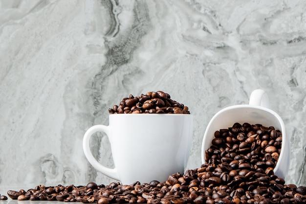Caffè nero in tazza e chicchi di caffè su marmo