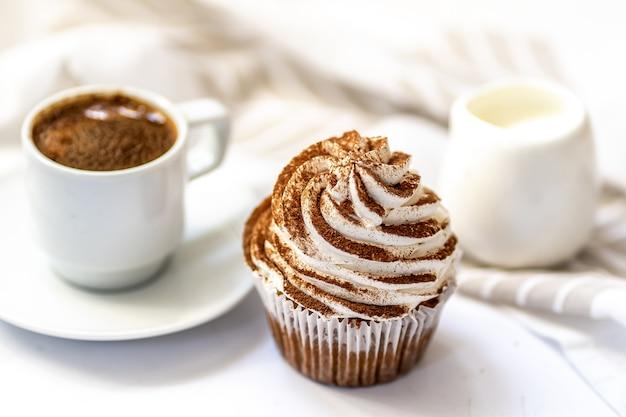 Caffè nero, una tazza con latte e un cupcake alle spezie con crema di formaggio e cacao su sfondo bianco