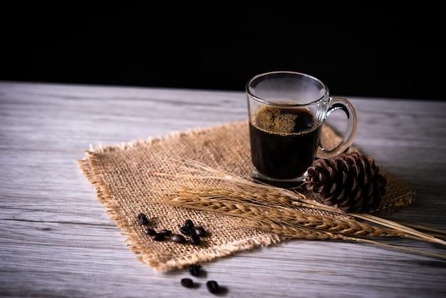 Il caffè nero in vetro è disposto sul pavimento di legno - natura morta di concetto