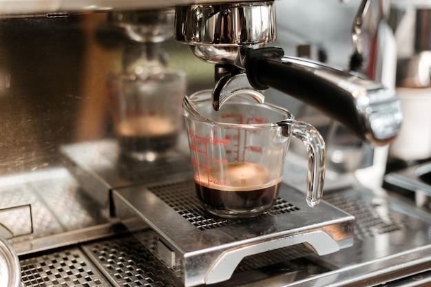 Caffè nero in misurino messo sulla macchinetta del caffè