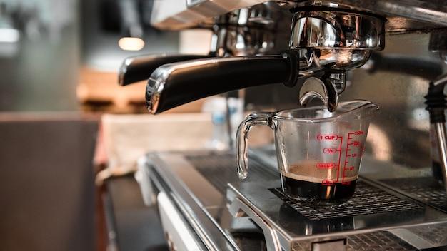 Caffè nero in misurino messo sulla caffettiera