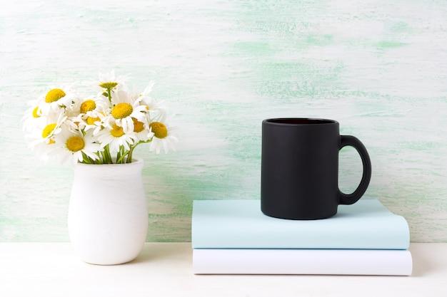 Tazza da caffè nero con bouquet di camomilla di campo bianco in vaso e libri rustici fatti a mano