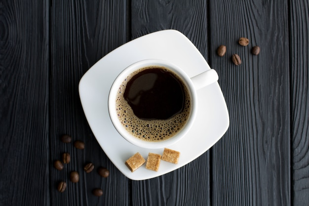 Caffè nero nella tazza bianca al centro del tavolo di legno nero. vista dall'alto. copia spazio. avvicinamento.