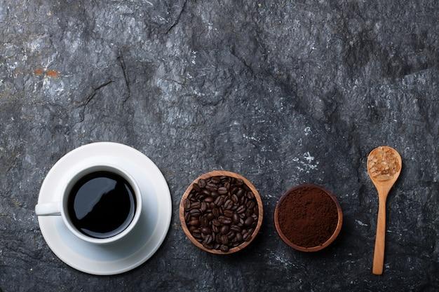Caffè nero nel chicco di caffè bianco della tazza nello zucchero di legno della tazza in cucchiaio di legno sulla pietra nera