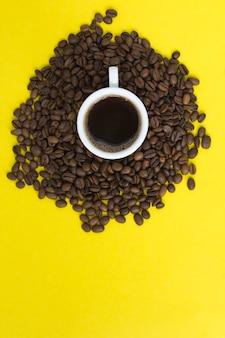 Caffè nero nella tazza bianca e chicchi di caffè. copia spazio. vista dall'alto.