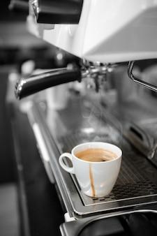 Il caffè nero in tazza bianca ha messo sopra la macchinetta del caffè