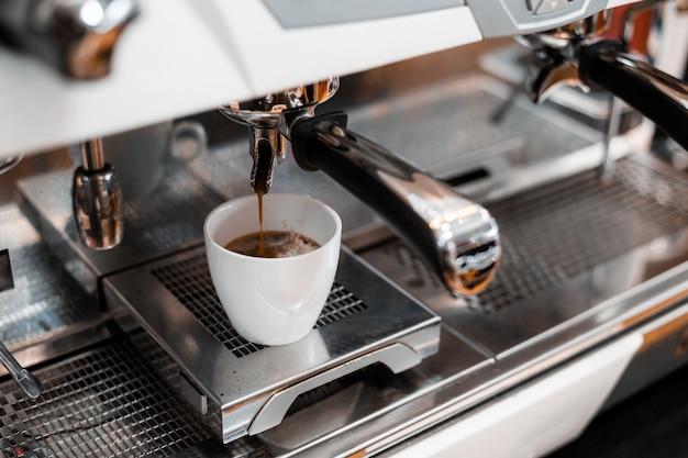 Caffè nero in tazza bianca messo sulla caffettiera