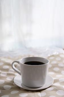 Caffè nero in una tazza bianca su un tavolo di stoffa a pois.